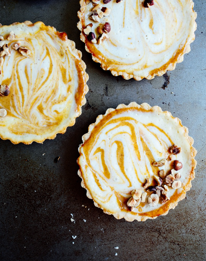 Pumpkin Cheesecake Tarts Recipe by The Wood and Spoon Blog by Kate Wood. These are simple, individual mini tarts made in removable bottom tart pans. An easy cheesecake and canned pumpkin puree filling swirled together with sugar and fall spices like cinnamon. The press in crust is easy to make and the whole thing is topped with sweet and salty walnuts or pecans or other nuts. Find this great dinner party dessert on thewoodandspoon.com