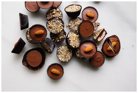 Homemade Chocolates Recipe by The Wood and Spoon Blog by Kate Wood. Learn how to make homemade chocolate in little wax candy cup wrappers. Kentucky bourbon balls topped with chopped pecans, peanut butter cups, and almond joy candies. These candies make a great gift or dessert for the chocolate lover in your life or valentine. Make these ahead and freeze. Simple way to make chocolate candy at home that taste like Reese's and mars candy and bourbon Balls. Find the recipe for making these chocolates in mini muffin tin on thewoodandspoon.com