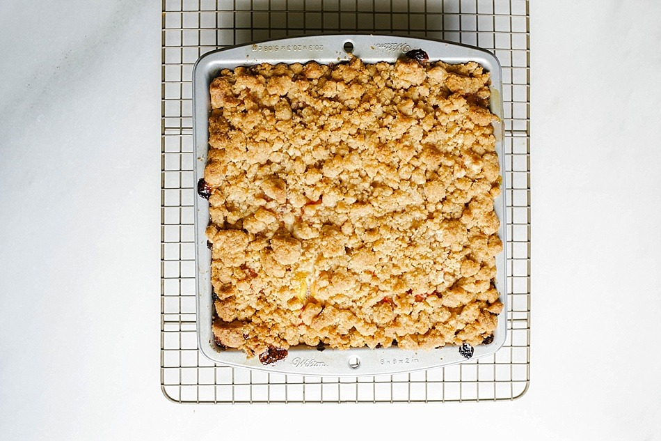 Raspberry Rhubarb Crumb Cake recipe by The Wood and Spoon Blog. A thick and fluffy sour cream cake filled with gooey raspberry and sweetened rhubarb. The whole cake is topped with a brown butter and sugar streusel crumb. This is a simple and easy summer cake that bakes quicky and can be easily adapted for a number of other summer berries, stone fruit, or other fruits. Find the recipe for this dessert like breakfast / snack cake at thewoodandspoon.com / woodandspoon.com .