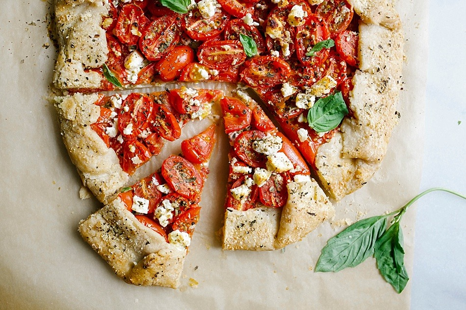 Tomato Galette with Pesto and Feta By The Wood and Spoon Blog by Kate Wood. This is a simply, flaky butter pie crust filled with ripe heirloom or Roma tomatoes, basil, pesto, and feta cheese. The whole thing is baked as a rustic galette style tart and is topped with parmesan cheese. This is a delicious way to use summer cherry tomatoes and a simple way to use pie crust. Find the recipe for this fun vegetable dinner or appetizer on thewoodandspoon.com
