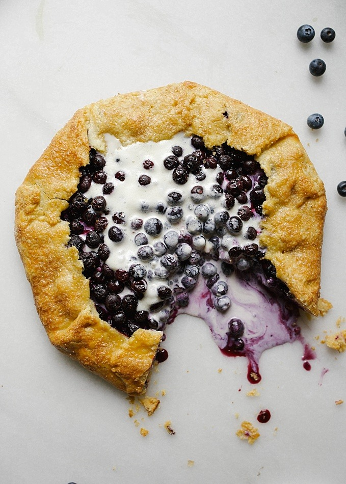 Blueberry Galette with a Cornmeal Crust Dessert Recipe by The Wood and Spoon Blog By Kate Wood. This is a simple, fast and easy recipe. Ripe, summer produce like blueberries and lemon are thick and juicy in this pie filling. The crust has cornmeal, flour, butter, and shortening, so it is flaky, golden and perfect every time pie crust. Serve on your summer holidays for a casual and rustic dessert. Serve with ice cream or whipped cream. You can substitute other fruit too like strawberries, peaches, or stone fruit in this galette. Find the recipe and more summer recipe inspiration at thewoodandspoon.com .