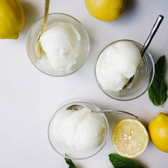 Lemon Mint Sorbet Recipe by The Wood and Spoon Blog by Kate Wood. This is a refreshing, frozen, lemon and mint sorbet made with freshly squeezed lemon juice, mint, and simple syrup. This ice cream is made in a ice cream maker and requires very little active prep time. Similar to a granita or frozen Italian ice, this treat is the perfect dessert to serve on a hot day! Find the recipe on thewoodandspoon.com