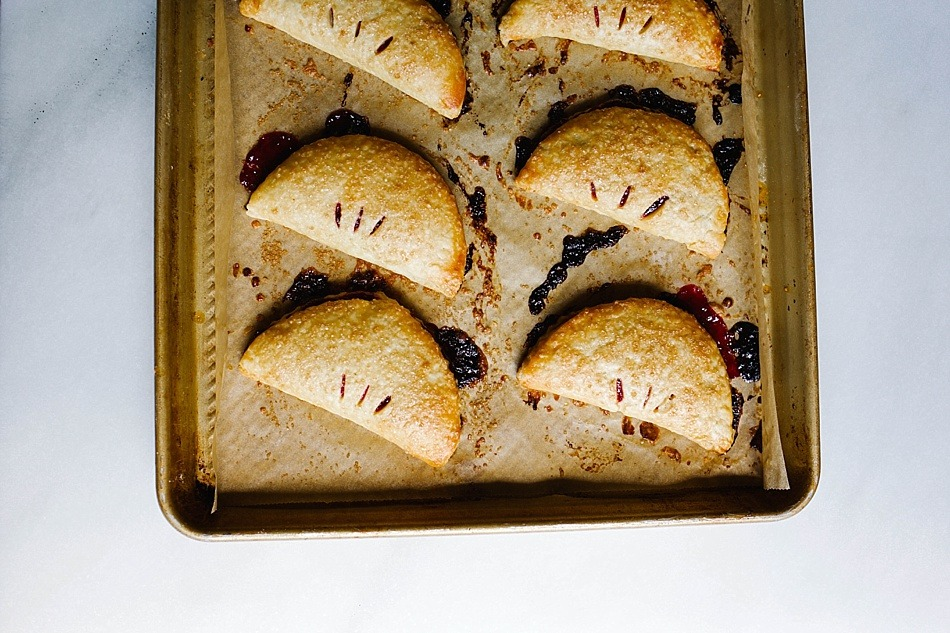Cherry Lime Hand Pies Recipe by The Wood and Spoon Blog by Kate Wood. This mini hand pies are personal pop tart desserts filled with ripe summer black and red cherries and zesty lime. A great alternative to fried pies, these desserts are sweet, make ahead, and use a buttery, homemade pie crust that gets flaky and delicious. The recipe is simple but learn all about how to make hand pies and homemade pop-tarts here on thewoodandspoon.com