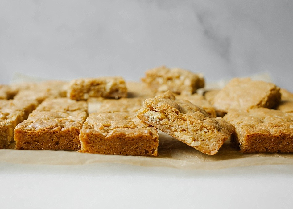 Brown Butter Blondies by The Wood and Spoon Blog by Kate Wood. This is a recipe for how to make brown butter blondies with a few different variations. First, a fluffy blondie filled with white chocolate chunks / chips and shredded sweetened coconut. Second, a snickerdoodle type blondie filled with cinnamon and sugar- rich, buttery, and delicious. These blondies can be whipped up in one bowl and serve a crowd. Perfect for tailgating, parties, or to make with kids. You can substitute your favorite toppings- nuts, chocolate chips, or toffee! Find the recipe and the how to on thewoodandspoon.com