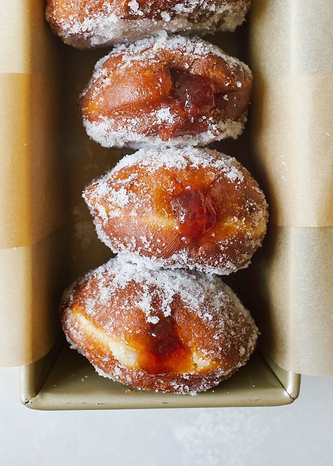 Jelly Donuts and a Saveur Blog Awards Nomination Recipe by The Wood and Spoon Blog by Kate Wood. Find the recipe for these fluffy yeast doughnuts filled with fruity jam and covered with sugar. These are fried donuts that are tossed in cinnamon sugar, powdered sugar, or granulated sugar. Find the recipe and the how to for these stuffed pastries (also known as Berliners) on thewoodandspoon.com