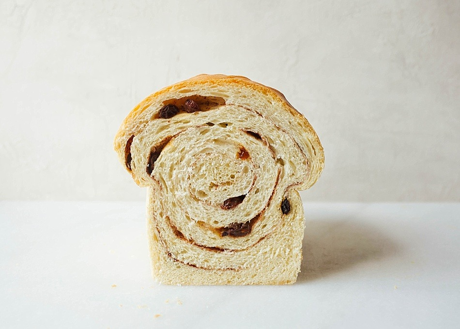 Raisin Swirl Bread Recipe by Kate Wood of The Wood and Spoon Blog. This is a recipe for 2 loaves of fluffy white bread swirled with cinnamon sugar and raisins. This bread makes delicious toast and is perfect for breakfast or casual dessert. You can freeze this bread to save for later and it is perfect for sharing. Learn to roll and shape this loaf of bread and read more about this delicious and simple yeast bread requiring egg and milk on thewoodandspoon.com