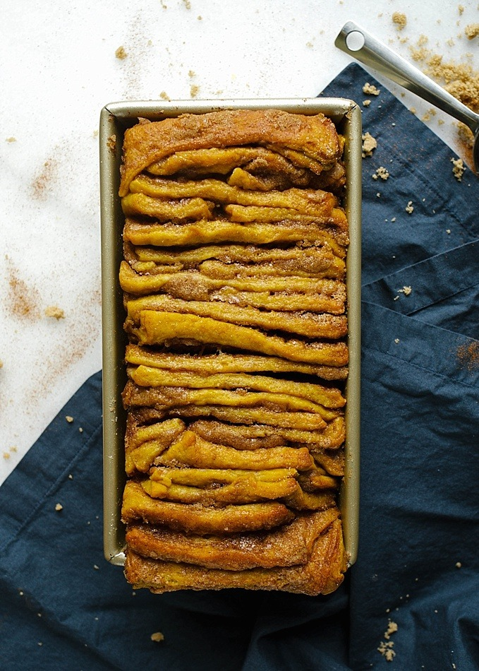 Pumpkin Pull-Apart Bread Recipe by The Wood and Spoon Blog by Kate Wood. This is a simple pull-apart bread adapted from Pioneer Woman cinnamon rolls. A kneaded dough seasoned with fall spices and filled with a gooey cinnamon sugar filling, this pumpkin pull apart bread is a treat for fall breakfasts and brunch. This is a great Thanksgiving dessert as well. The yeast bread is baked and glazed with a tangy cream cheese glaze / frosting. Find the recipe and how to on thewoodandspoon.com for this virtual pumpkin party.