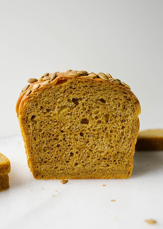 Pumpkin Yeast Bread Recipe by The Wood and Spoon Blog by Kate Wood. This is a fluffy, simple, sandwich yeast bread seasoned with cinnamon, pumpkin puree, and seeds. Perfect for the holidays, thanksgiving and christmas leftovers, this bread is excellent for toast and snacking and makes and excellent idea for hostess host gift. Find the recipe and more info on how to make bread without a bread machine maker on thewoodandspoon.com