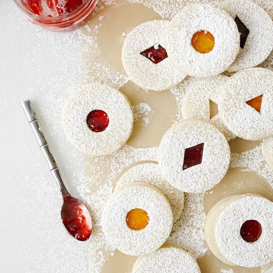Raspberry Lemon Linzer Cookies recipe by The Wood and Spoon blog by Kate Wood. This is a classic linzer cookie recipe made with almond flour and all-purpose flour. The cookies are scented with lemon zest and are filled with a raspberry jam. The dough is cut out with cookie cutters. Sprinkle the tops of these Christmas baked goods with powdered sugar. These are what to bring to holiday or Christmas party / exchange. Find the recipe and the how to on thewoodandspoon.com