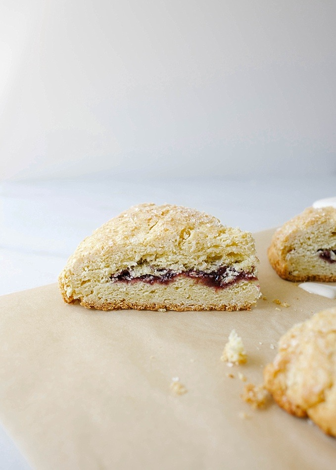 Jam-Filled Scones by Wood and Spoon Blog. These are tender and rich cake scones, perfect for morning breakfast or brunch. This recipe makes buttery brown edges and is soft from the cream. The scones are stuffed with jelly of choice and topping with sugar. Find the recipe for the tea party favorite on thewoodandspoon.com