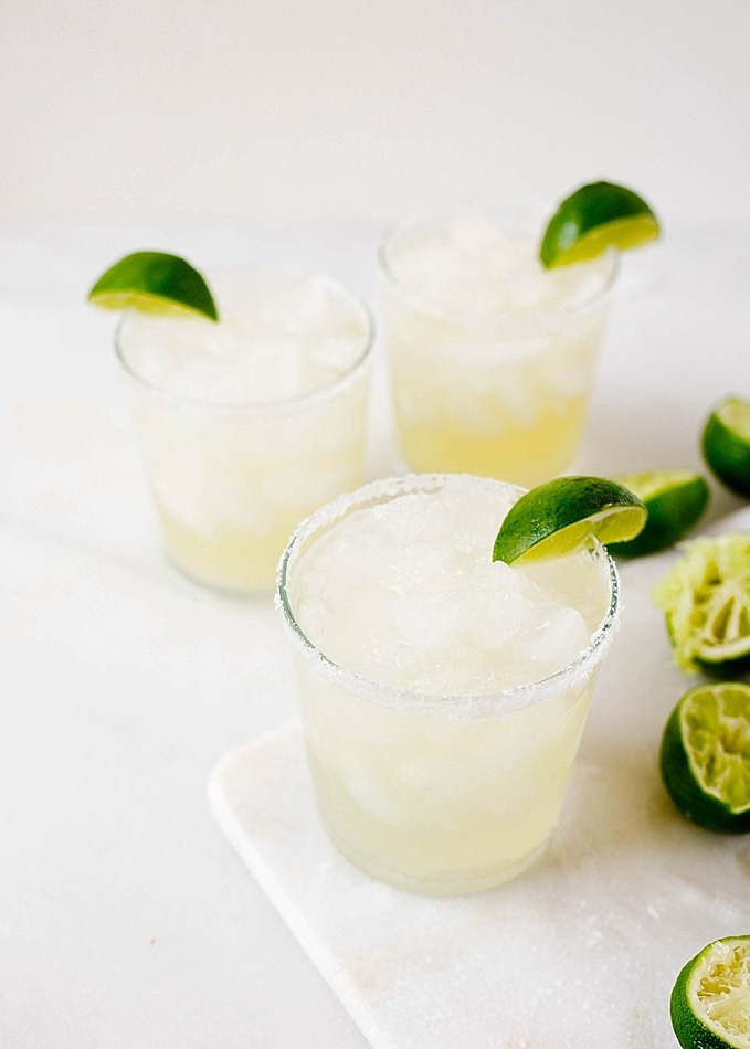 Ginger Margaritas made with a fresh spicy ginger simple syrup, fresh lime juice, and tequila blanco. These refreshing summer cocktails can be batched to serve a crowd and can easily be made ahead. Perfect poolside beverage or for serving at fiesta themed parties. Find the recipe and how-to on thewoodandspoon.com