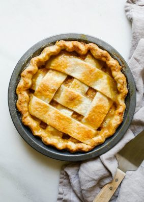 "Peach Lattice Pie by Wood and Spoon blog. This is an all butter double pie crust with bourbon filled with cinnamon and vanilla bean peaches, all baked into a classic southern pie. the recipe is from Amber Wilson of ""For the love of the south"" cookbook. Find the recipe and how to for this chunky lattice summer dessert on thewoodandspoon.com by Kate wood."