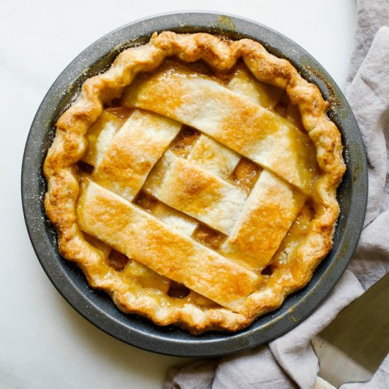 """Peach Lattice Pie by Wood and Spoon blog. This is an all butter double pie crust with bourbon filled with cinnamon and vanilla bean peaches, all baked into a classic southern pie. the recipe is from Amber Wilson of """"For the love of the south"""" cookbook. Find the recipe and how to for this chunky lattice summer dessert on thewoodandspoon.com by Kate wood."""