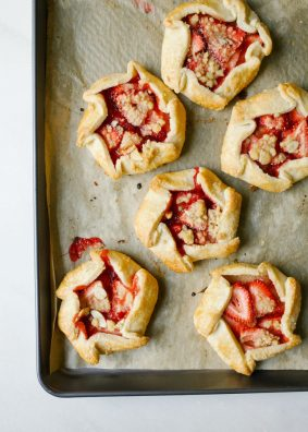 Mini Strawberry Galettes by Wood and Spoon blog. These are small open hand pies made with a simple butter dough and filled with fresh strawberries. On top an easy almond crumble adorns each dessert and a sprinkle of powdered sugar finishes them off. These little personal sized desserts are a special was to use summer produce and are sure to impress friends at parties. Find the recipe and how to on thewoodandspoon.com