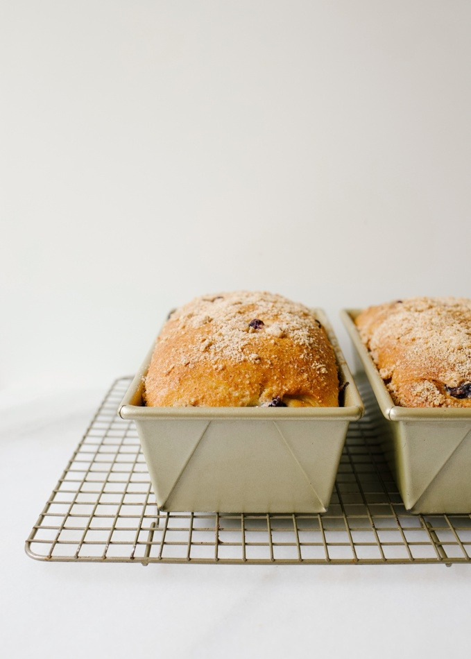 Blueberry Brioche recipe by Wood and Spoon blog. This is a recipe for two yeast loaves of brioche made with butter, egg, and a smidge of sugar. The fluffy white bread is studded with blueberries and seasoned with cinnamon. Each loaf has an optional crumble topping for extra sweet and salty in each bite. Learn how to fold and create this beautiful homemade breakfast treat here at thewoodandspoon.com by Kate Wood.