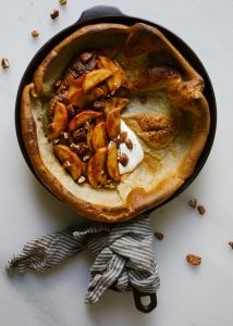 Pecan Apple Dutch Baby by Wood and Spoon. This is a cinnamon flavored skillet pancake topped with cinnamon spiced apples and maple glazed pecans. This one bowl recipe can be make in a pinch and is a fun breakfast to make with kids. Watch this simple treat rise In the oven and top it with fall-flavored fruit and crunchy, sweet and salty nuts. Find the recipe and how-to on thewoodandspoon.com
