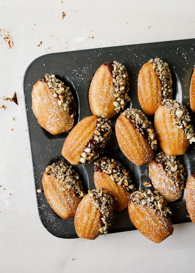 Brown Butter Bourbon Madeleines with Dark Chocolate Ganache and Pecans. These are buttery French cookies filled with booze, butter, and topped with decadent rich bourbon ganache. Each little treat is fluffy, like a cake meets cookie and it topped with yummy toppings. These make terrific fall treats for cocktail parties or gifts. These traditional bakes are sweet and elegant and a fun treat to learn how to make! Learn more on thewoodandspoon.com by Kate Wood!