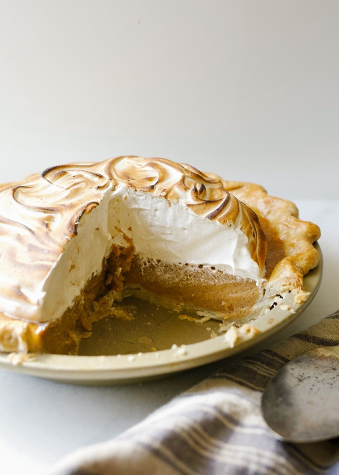 Sweet Potato Meringue Pie by Wood and Spoon blog. This is a butter and shortening pie crust blind baked and filled with a sweet potato, pumpkin tasting filling, cinnamon, and warm spices. The topping is a brown sugar and cinnamon marshmallow meringue that is cooked on the stove and whipped to stiff peaks. The whole thing is torched for a toasty golden finish. Read more about this fall autumn favorite pie for holidays (especially thanksgiving!) on thewoodandspoon.com by Kate Wood