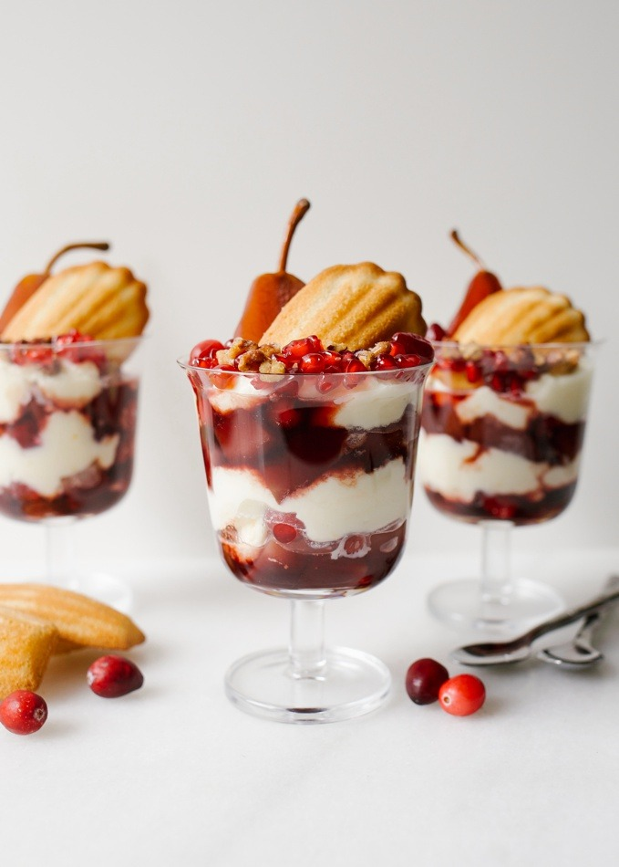 Poached Pear Trifles with wine pears, cranberries, pomegranate, Donsuemor madeleines and a creamy whipped filling. These trifles are sweet and tangy and boozy all at the same time. First up are red wine and cinnamon poached pears and cranberries that are cooked until soft. These are layered with a cream cheese or mascarpone whipped filling scented with orange zest, French madeleines, and more fresh fruit! Make these treats for a fancy holiday gathering. You can make large trifles or smaller individual ones. Recipe on thewoodandspoon.com by Kate Wood