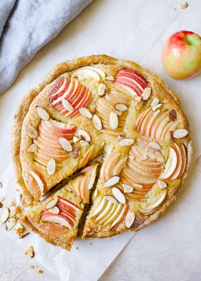 Apple Frangipane Tart by Wood and Spoon blog. This is an elegant holiday tart with a flaky pie crust, and almond filling and beautiful apples on top. Served with a glass of wine this is the French treat your holiday guests will go crazy for! This fancy dessert is made in a tart pan and easily serves a crowd. Find out more about the recipe on thewoodandspoon.com