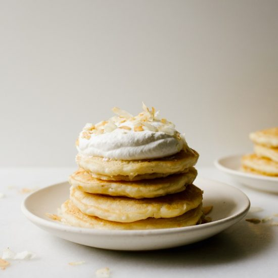 Almost Vegan Coconut White Chocolate Pancakes recipe by Wood and spoon. These are coconut oil pancakes sweetened with dried flaked coconut and white chocolate! The pancakes are light and fluffy and flavored with coconut thanks to the coconut milk. Top with coconut whipped cream or fresh fruit compote for a delicious healthy breakfast that actually heat well too! Find this vegetarian recipe on thewoodandspoon.com brunch