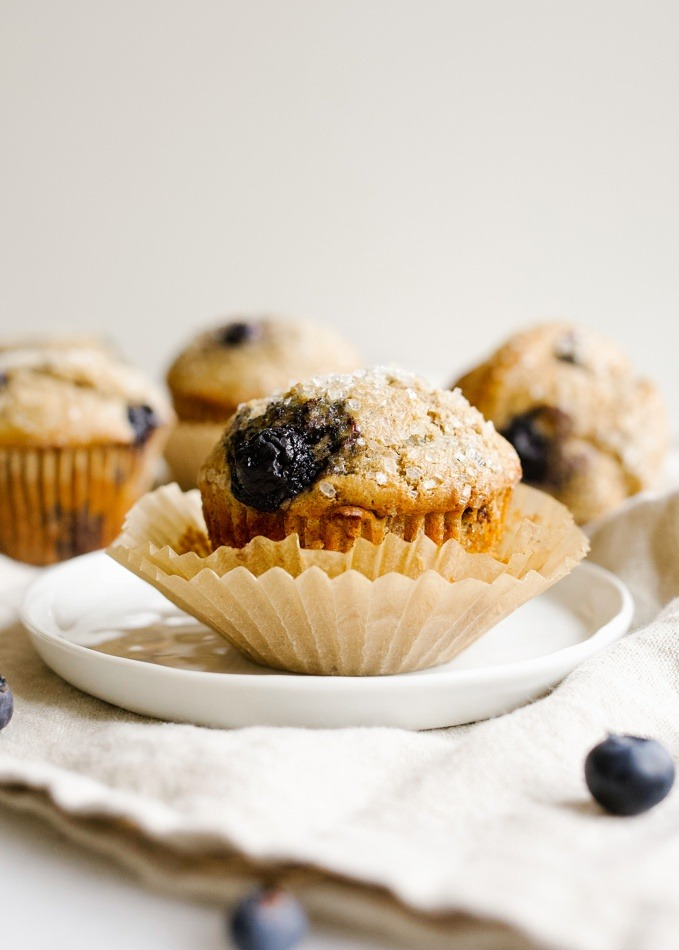 Whole Wheat Blueberry Muffins Recipe by Wood and Spoon. This is a healthy breakfast pastry featuring 100% whole wheat flour and an option for reduced sugar! The cake is sweeter extra with fresh or frozen blueberries and ends up being a fluffy treat with a big domed top. Feel good about your lighter morning foods with this baked good. Read more on thewoodandspoon.com by Kate wood
