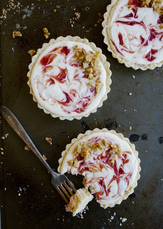 White Chocolate Cheesecake Tartlets with Blood Orange Swirl by Wood and Spoon Blog by Kate Wood. These are almost shortbread tart crusts filled with a no bake cream cheese and white chocolate filling. The quick blood orange jam here adds a swirl or flavor and tang. You can substitute in another favorite jam here! These come together quickly and make for a nice make-ahead dessert option for small dinner parties. They are an easy to make simple fancy dessert for the spring! If you're wondering how to use blood oranges, this is how! Read more on thewoodandspoon.com