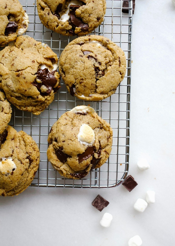 Vegan Fluffernutter Cookies by Wood and Spoon blog. These are egg and dairy free cookies with a peanut butter base stuffed with marshmallows, dark chocolate and loads of flavor! They use a flaxseed or chia egg in place of regular ones and coconut oil in place of butter. They are chewy and full of delicious flavor. Find the recipe for this vegetarian cookie on thewoodandspoon.com by Kate Wood healthy!