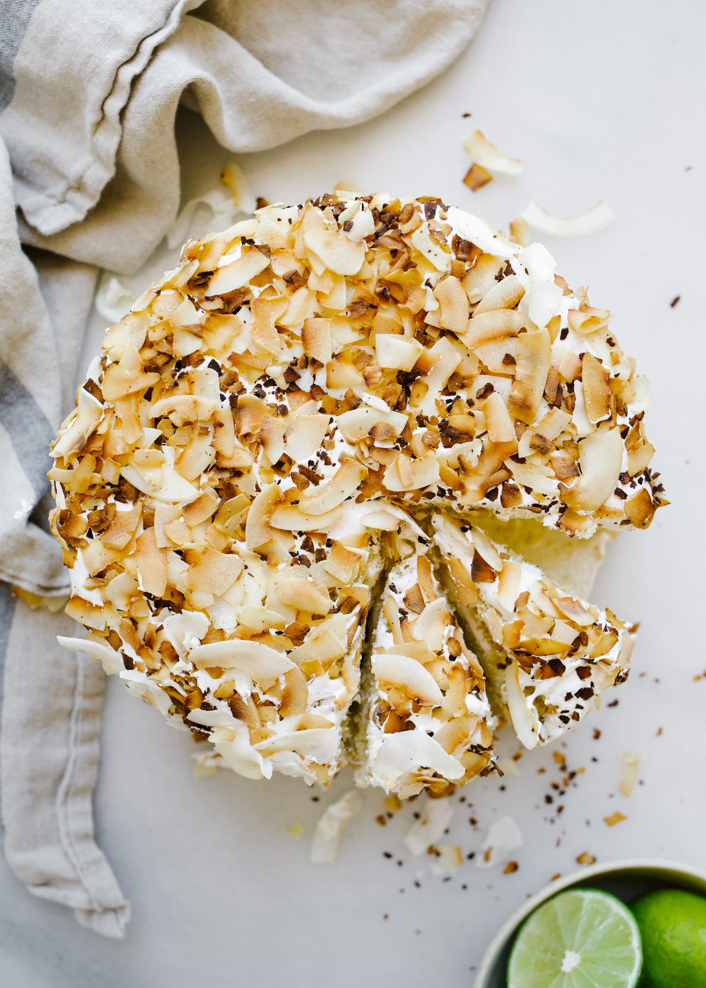 Coconut Key Lime Cake by Wood and Spoon. This is a lime zest scented fluffy butter cake with a coconut marshmallow 7 minute egg white frosting and coated in toasted flaked coconut. This cake tastes like summer but is great for spring parties and gatherings. Serve this to a crowd or try out a cream cheese coconut frosting instead! Find the recipe and learn how to make this 3 tiered layer cake on thewoodandspoon.com