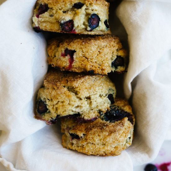 Chamomile Blueberry Scones by Wood and Spoon. These are fluffy cream and butter scones with sugared tops and an infusion of tea flavor. Blueberries are juicy throughout and flavor this richly scented breakfast treat. Perfect to share with coffee or tea. Find more about this recipe from Modest Marce on thewoodandspoon.com