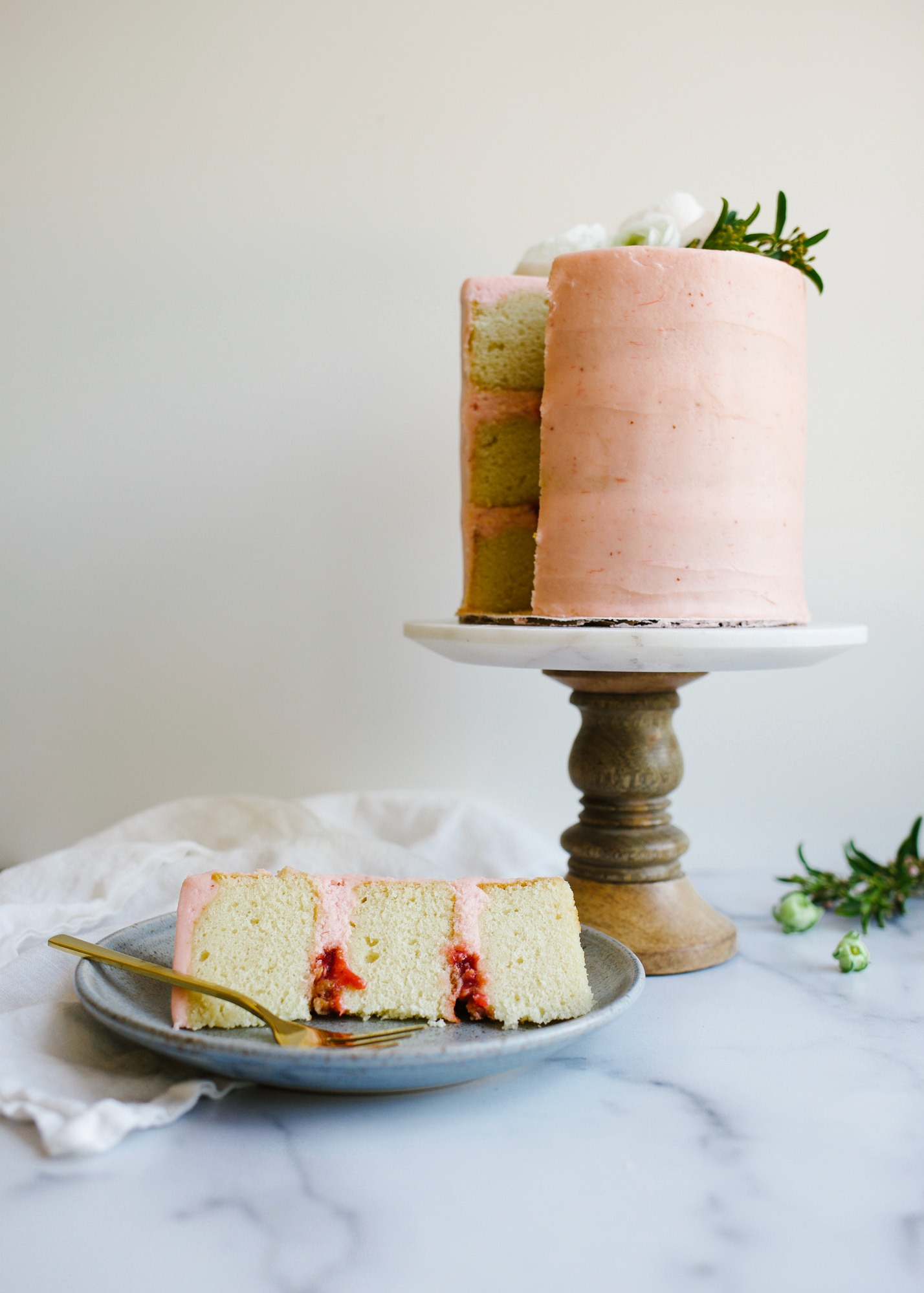 Vanilla Rhubarb Layer Cake by Wood and Spoon. These are vanilla cake layers filled with a rhubarb jam, an oatmeal streusel, and frosted with a rhubarb buttercream. This cake takes on pink color with it's fruit filled icing and stays soft and moist. Perfect for spring and summer parties and celebrations. Find out how to make this naked layer cake on thewoodandspoon.com