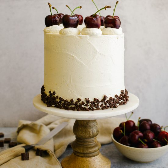 Cherry Chip Cake recipe by wood and spoon. This is a vanilla cake with cherries and mini chocolate chips filled with a quick dark cherry filling and coated with a tangy cream cheese American buttercream. The cake is a great summer layer cake for parties and cake be made in advance. The frosting is stable and compliments the cherries and chocolate well. Find the recipe and learn more about stacking layer cakes on thewoodandspoon.com