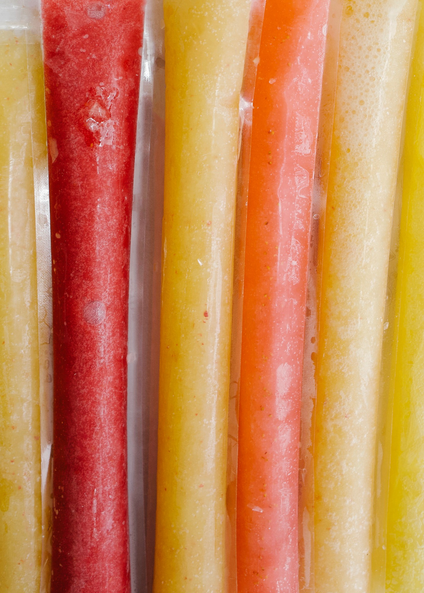 Champagne Cocktail Popsicles by Wood and Spoon. Learn to make homemade mimosa push pops, Bellini popsicles, and strawberry lime champagne frozen treats! These are made in plastic sleeves with fresh real strawberries, peaches, and orange juice and sparkling wine. Find the recipe and learn how to make these boozy summertime frozen desserts on thewoodandspoon.com