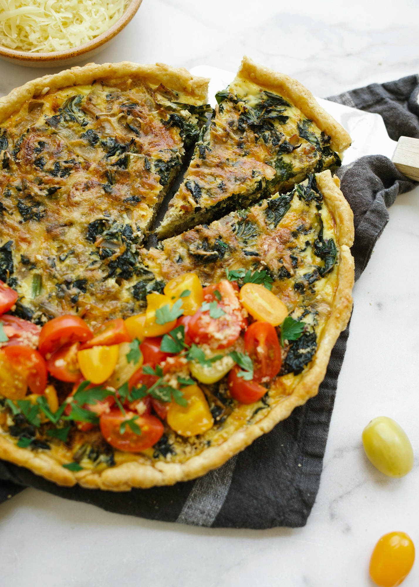 Kale Swiss and Sausage Quiche by Wood and Spoon blog. An all butter pie crust filled with a smoky Italian sausage, kale greens, and Kerrygold swiss cheese. topped with fresh tomatoes, balsamic glaze, and herbs. perfect for breakfast brunch or supper. find the simple fresh recipe on thewoodandspoon.com by Kate Wood