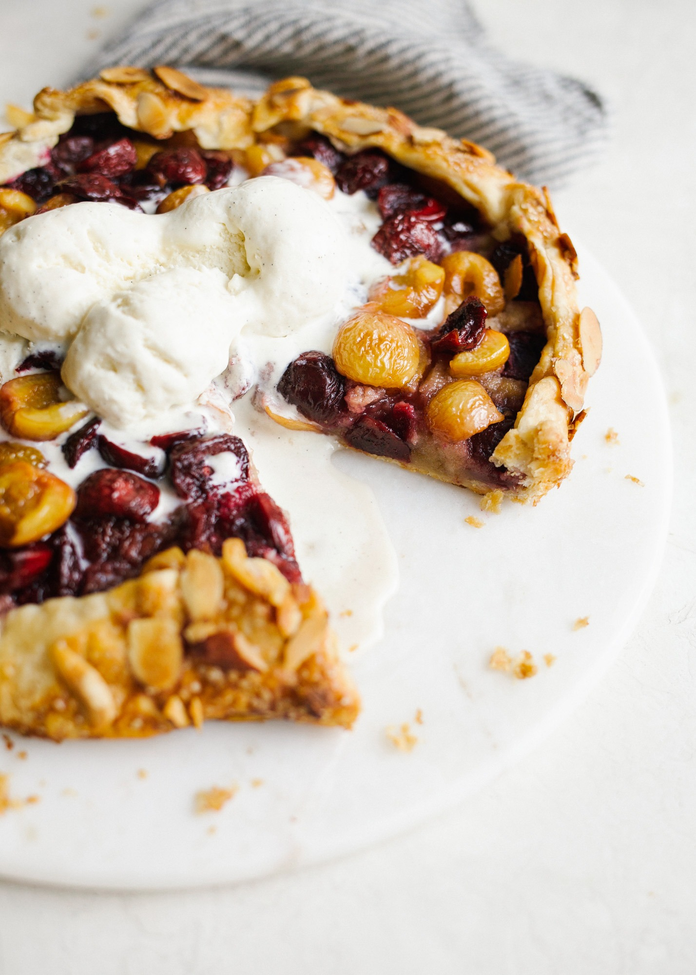 Cherry Almond Galette by Wood and Spoon. This is an all-butter pie crust filled with seasonal rainier and dark cherries and an almond meal frangipane filing. Top with ice cream and serve wedge slices as a summer dessert perfect for picnics and parties. Find more about this simple pie recipe on thewoodandspoon.com