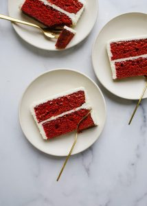 Red Velvet Cake by Wood and Spoon blog. This is a cocoa flavored layer cake with a tangy cream cheese frosting. This recipe is fluffy and festive with bright red layers and is perfect for holiday baking or birthday celebrations. Learn more about how to make this dessert on thewoodandspoon.com by Kate Wood