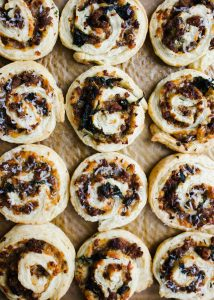 Sausage Kale Pinwheels by Wood and Spoon. These are simple pastry roll up filled with spicy italian sausage, kale, cheese, and herbs. These make great breakfast bites or afternoon snacks / appetizers. The dough is simple and requires no rising time. Think of it as a no-rise yeast dough! Learn how to make these yummy make ahead feed a crowd savory treats on thewoodandspoon.com