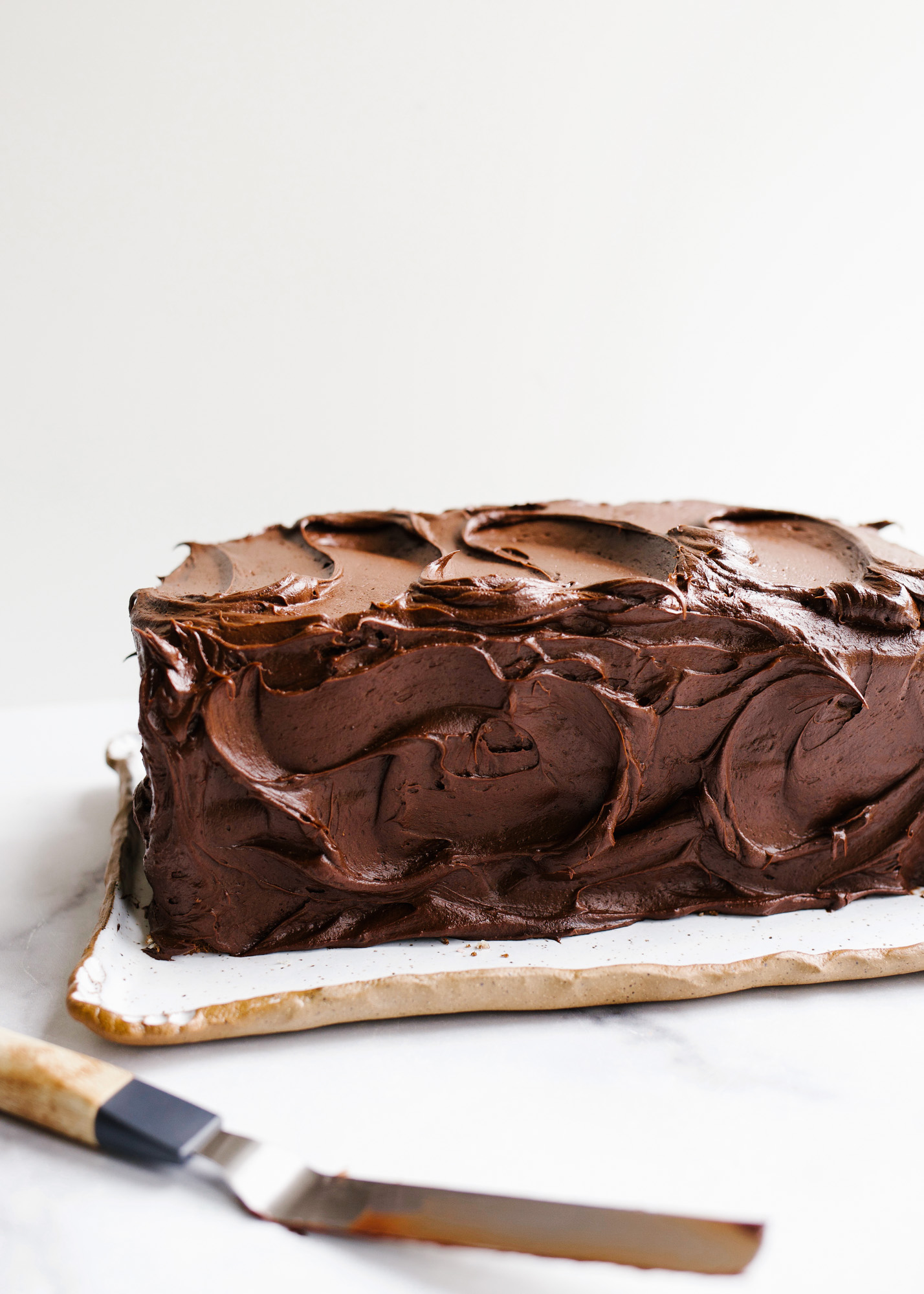 Marble Layer Cake by Wood and Spoon blog. This is a small batch mini chocolate and vanilla swirl cake with a rich fudge frosting. Perfect for smaller serving size or family size. This cake can be made as a sheet cake or a small stacked cake. Learn how to swirl cake batters and make this delicious half and half cake on thewoodandspoon.com