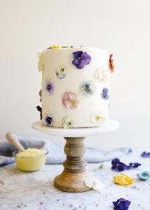 Lavender Cake with Lemon Curd and Creamy Vanilla Frosting by Wood and Spoon blog. This is a floral cake decorated with edible dried flowers and filled with a homemade lemon curd. This sturdy lavender cake is coated in fluffy American whipped buttercream. Learn how to make this beautiful layer cake for the spring on thewoodandspoon.com