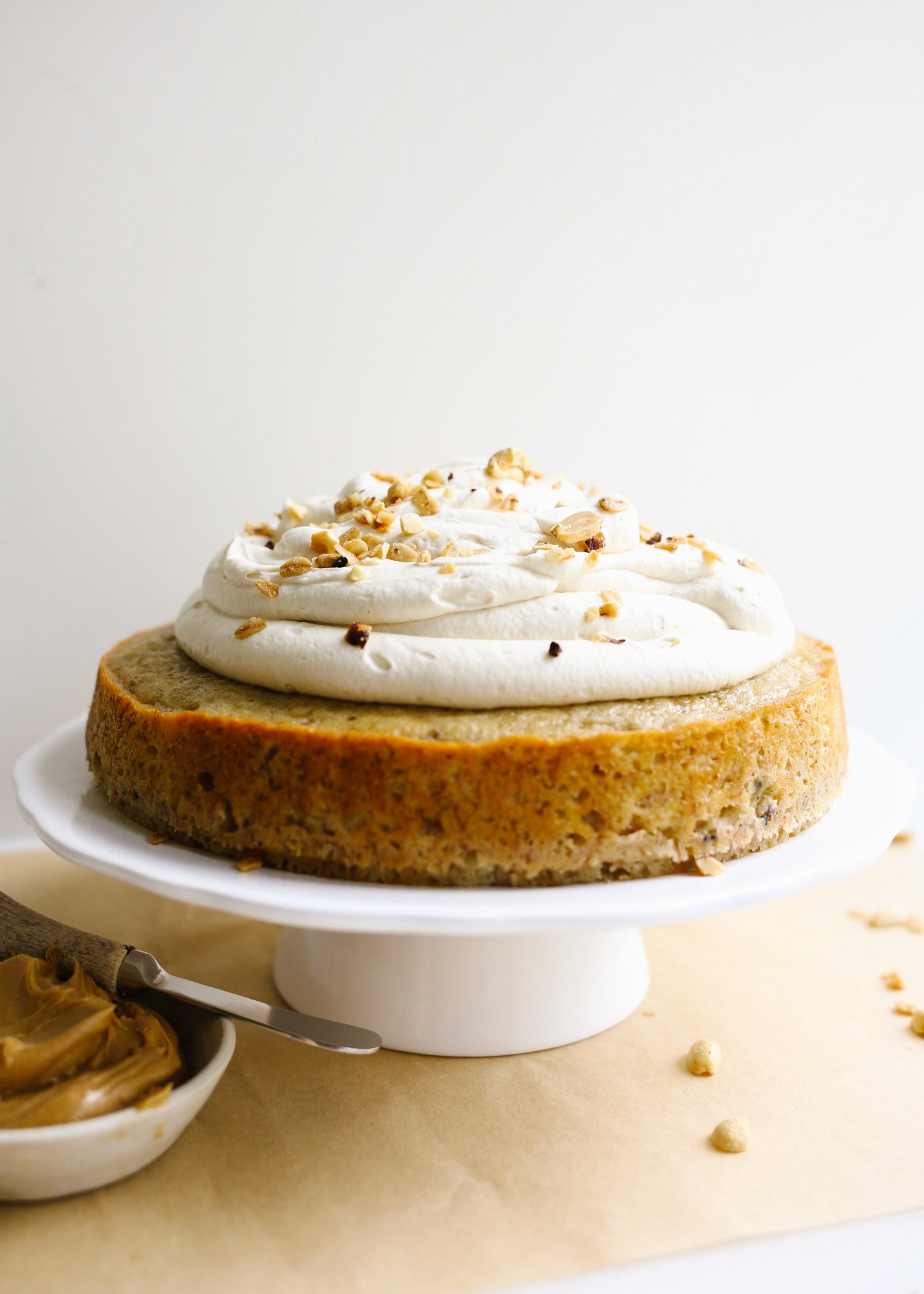 Banana Bread Cake with Peanut Butter Whipped Cream by Wood and Spoon blog. This is a moist one bowl banana bread made in a cake pan and topped with a fluffy peanut butter whipped cream. The cake can be made in a loaf or round pan and can be frozen, made ahead, and served as breakfast or dessert.