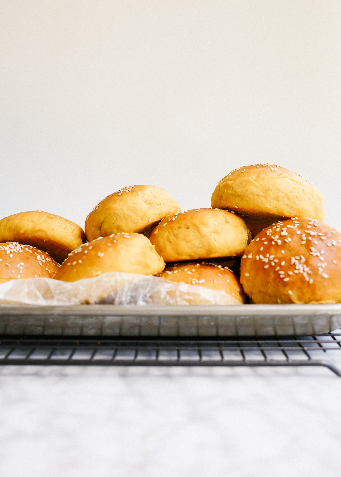 Sweet Potato Buns by Wood and Spoon blog. These are fluffy potato hamburger buns using mashed sweet potato. They are thick and tender and would be terrific with burgers, barbecue, or Thanksgiving leftover sandwiches! Find out how to make this simple homemade yeast bread rolls on thewoodandspoon.com