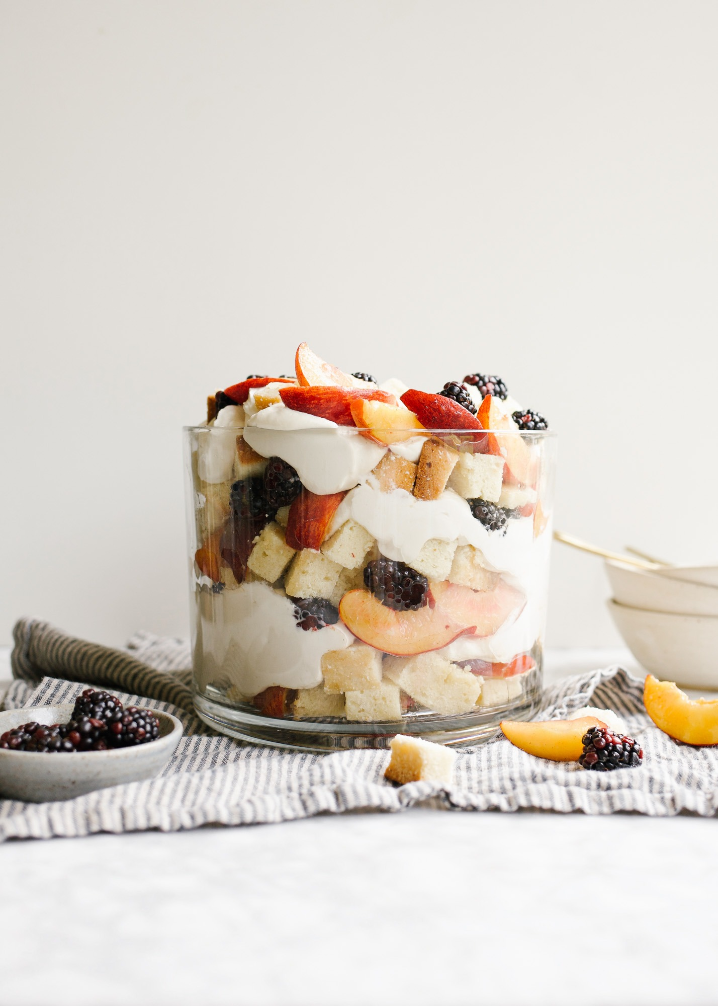 Peaches and Cream Trifle by Wood and Spoon blog. This trifle features homemade pound cake, a cream cheese whipped cream, and fresh sugared summer peaches. Add a few berries or you other favorite summer fruit to make this a festive and colorful dessert to serve a crowd for warm weather gatherings. You can make this ahead or use store-bought pound cake! Find more about the recipe on thewoodandspoon.com
