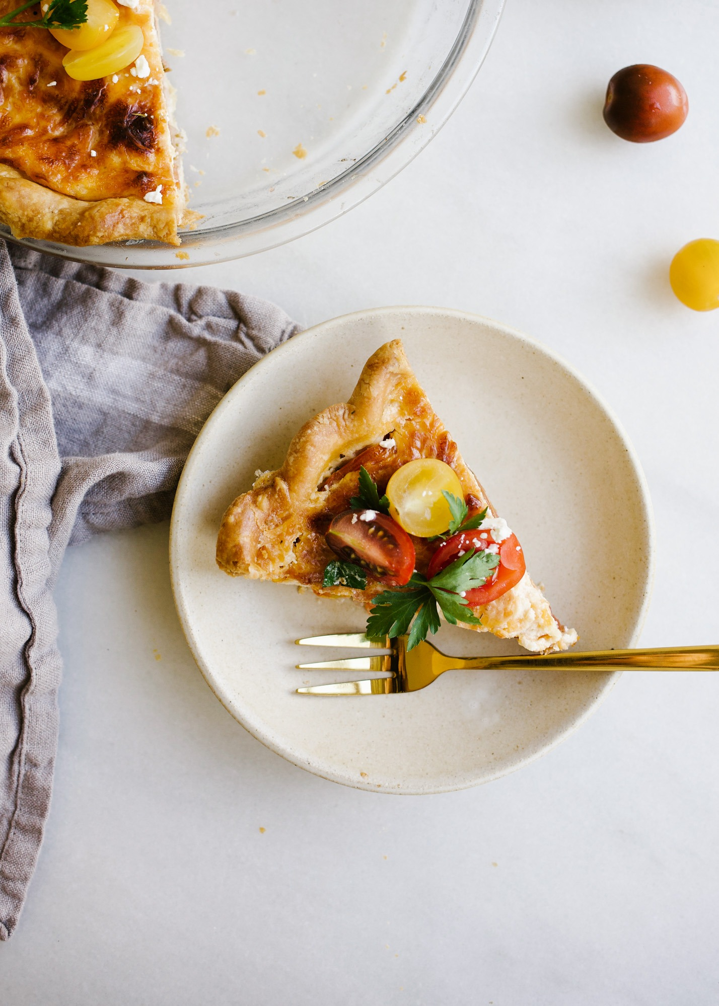 Tomato Pie by Wood and Spoon. This is a simple summer pie of fresh farm tomatoes, cheddar cheese, Italian herbs, and a buttery flaky crust! Learn how simple it is to make this savory pie that makes for a terrific lunch or dinner option! Serve this pie for summer gatherings! Learn more on thewoodandspoon.com