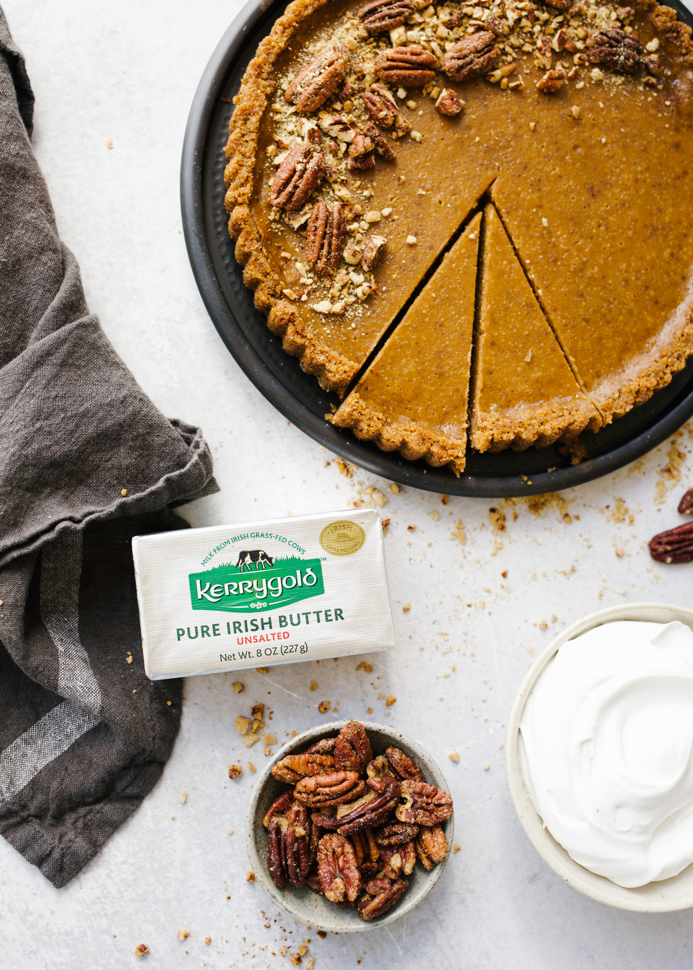 Sweet Potato Pie Tart with Candied Pecans and Marshmallow Whipped Cream by Wood and Spoon blog. A simple pumpkin pie-esque tart made with sugared nuts, a nuts and graham cracker crust, and a fluffy sweetened whipped cream topping! This is a terrific southern holiday favorite dessert to make during thanksgiving and Christmas winter months and is a beautiful take on the classic treat. Learn how to make them on thewoodandspoon.com