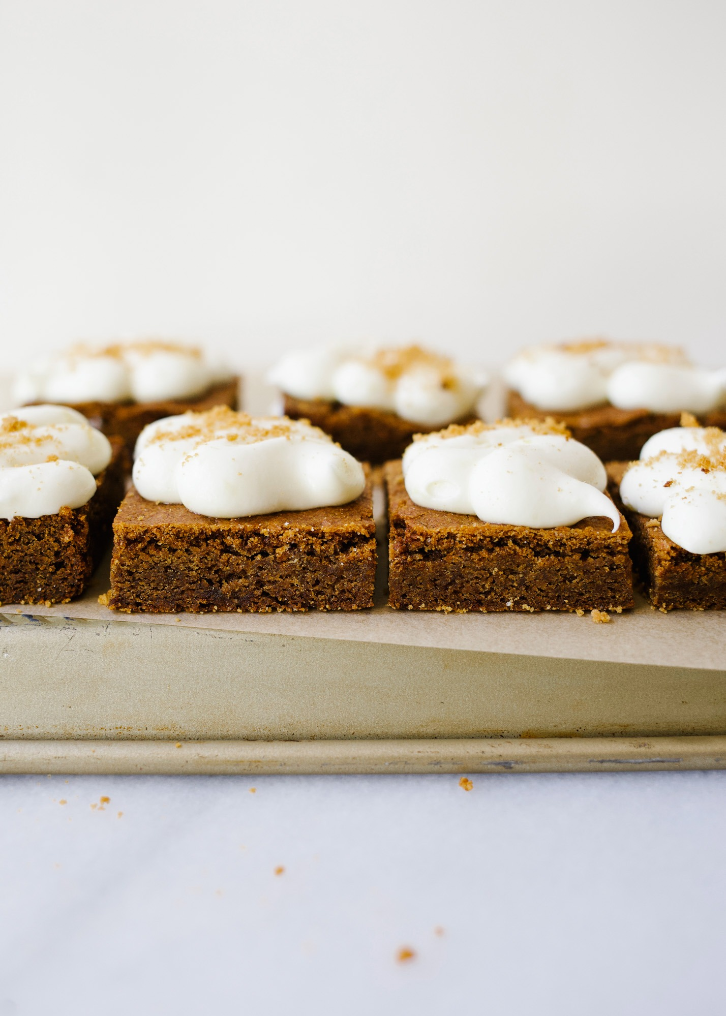 Chewy Gingerbread Lemon Bars by Wood and Spoon. These are soft blondie-like bars flavored with ginger and topped with a cream cheese and lemon frosting! These bars and sweetened and chewy, perfect for the holidays! Learn how to make these sweet gingerbread treats on thewoodandspoon.com