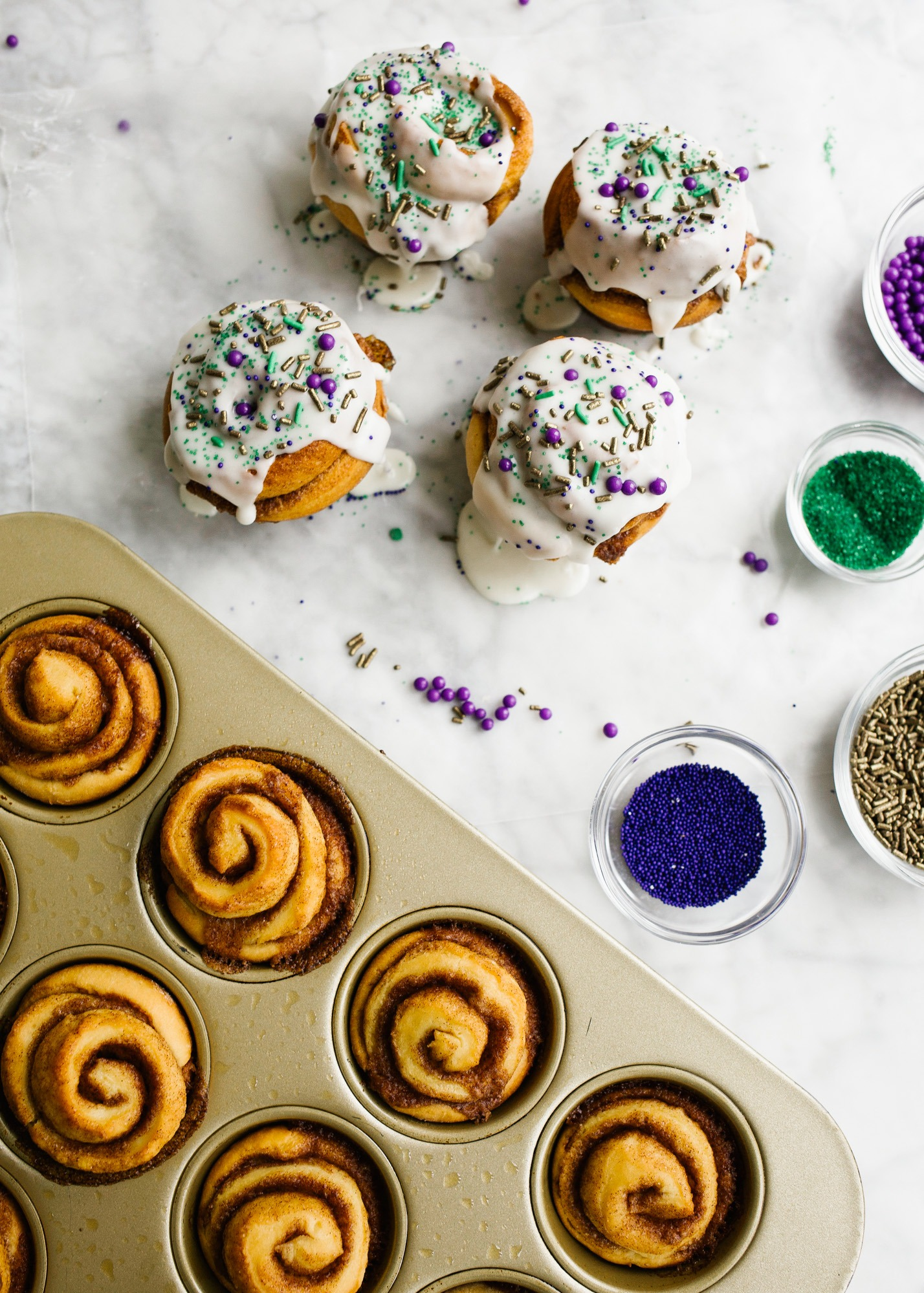 King Cake Cinnamon Rolls by Wood and Spoon blog. This is a recipe for brioche style cinnamon rolls filled with a cinnamon brown sugar filling and topped with a thick or thin powdered sugar icing glaze. Each roll is topped with festive Mardi Gras sprinkles as homage to the original king cakes! Celebrate the mardi gras season with these yummy breakfast or dessert rolls on thewoodandspoon.com