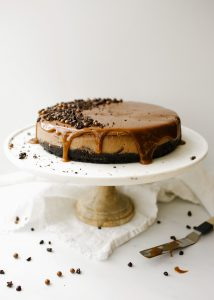 Chocolate Mascarpone Cheesecake by Wood and Spoon blog. This is a creamy chocolate cheesecake made with mascarpone cheese, a chocolate sandwich cookie Oreo crust, and a rich caramel topping. The crust is scented with espresso powder and lends a buttery crunch to the otherwise smooth dessert. This is a decadent treat for chocolate lovers and a great alternative to a cream cheese cheesecake. Learn how to make it on thewoodandspoon.com