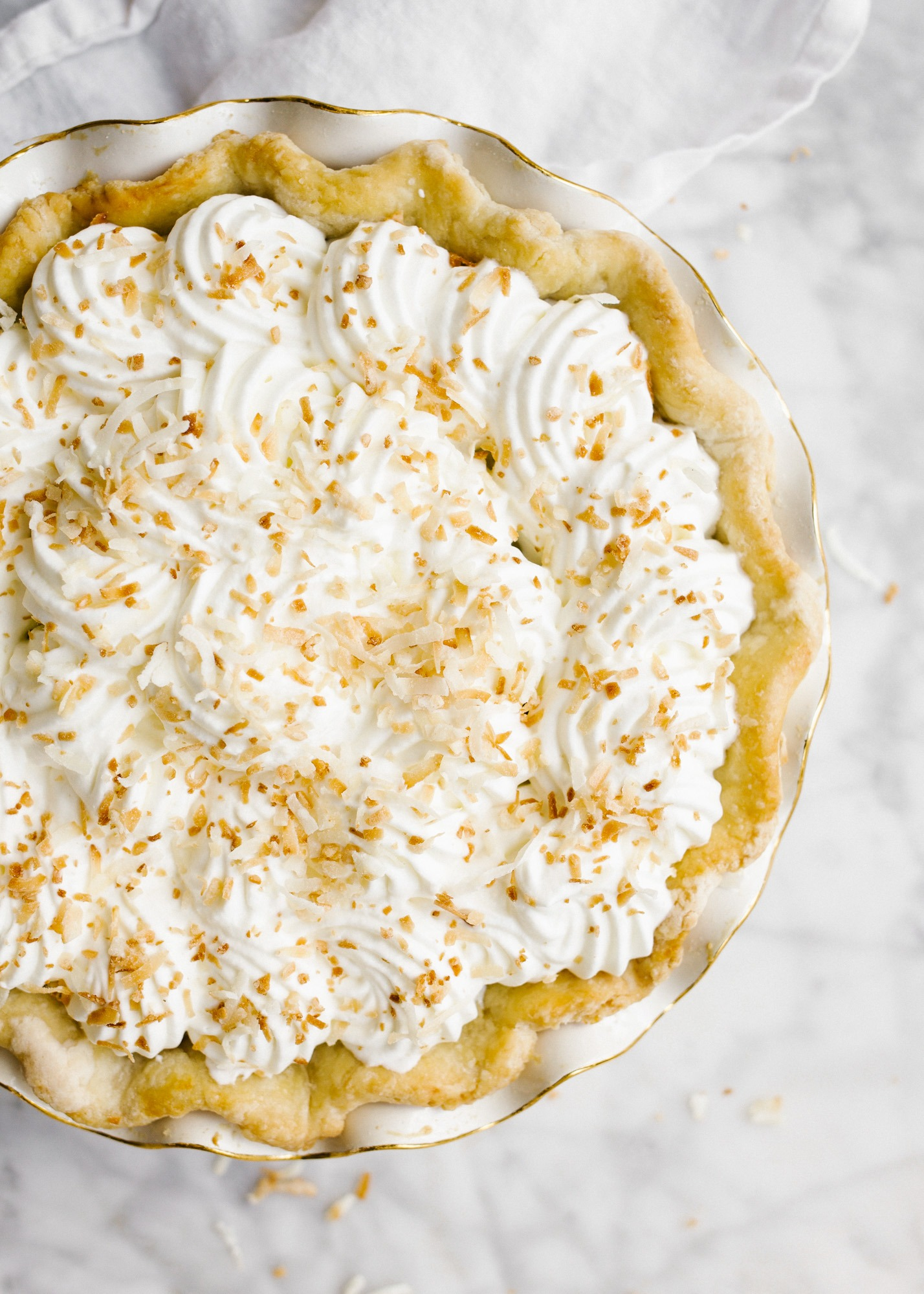 Southern Coconut Cream Pie and our Trip to the Exumas. This is a stovetop vanilla custard pie flavored with sweetened coconut flakes and topped with a homemade whipped cream. The butter and shortening flaky pie crust is filled with the coconut milk filling and it makes for a delicious summertime or spring tropical flavored bake ahead pie for dessert. Learn how simple it is to make southern pies on thewoodandspoon.com