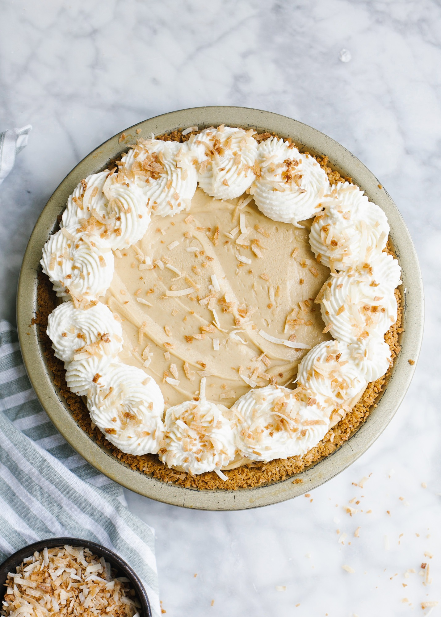 Peanut Butter Coconut Pie by Wood and Spoon blog. This is a fluffy icebox pie made with creamy peanut butter and loads of creamy coconut flavor. The crust can be made with sweetened coconut flakes, butter and either graham crackers or vanilla wafers. This is a quick and simple dessert to make for peanut butter lovers! Find the recipe and how-to on thewoodandspoon.com