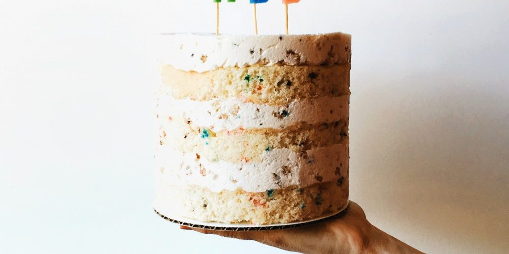 Confetti ice cream cake recipe by The wood and spoon blog by Kate wood. This is a simple funfetti cake recipe inspired by momofuku milk bar by christina tosi. The cake is make and layered in a naked style with a no churn cream cheese cake batter ice cream with sprinkles. There's also a salty cake mix crumb inside the cake. This is a fun birthday cake or frozen celebration cake that will serve a crowd and is very festive. Find the recipe and how to make a layered naked cake on thewoodandspoon.com